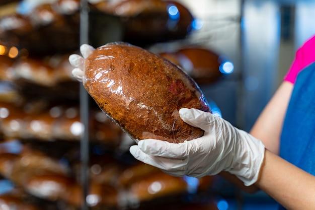 工業用オーブンの背景にパン屋の手でパンとパンの棚。工業用パンの生産。