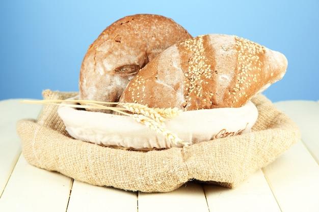 색상에 나무 테이블에 고리 버들 세공 바구니에 빵