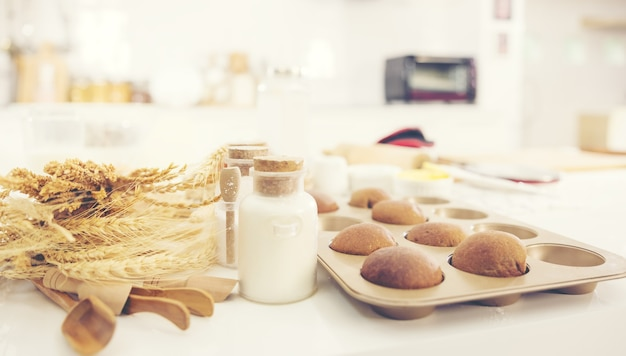 Bread in kitchen, baking ingredients placed on wooden table, ready for cooking. copyspace for text. concept of food preparation, kitchen on background.