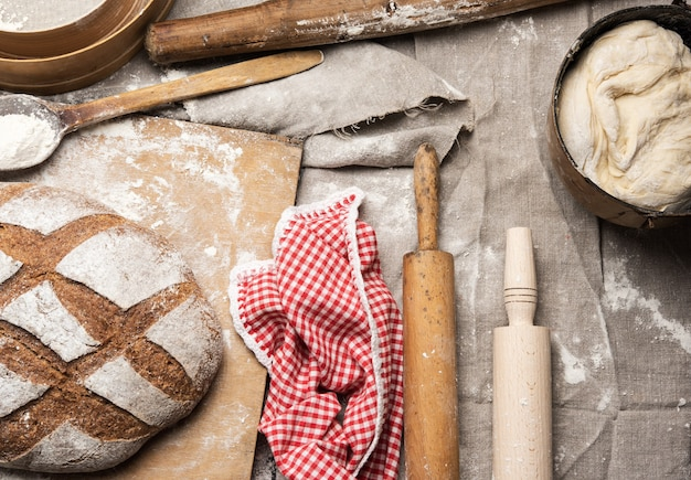 Bread, kneaded dough of white wheat flour lies on a metal bucket and a wooden rolling pin, top view