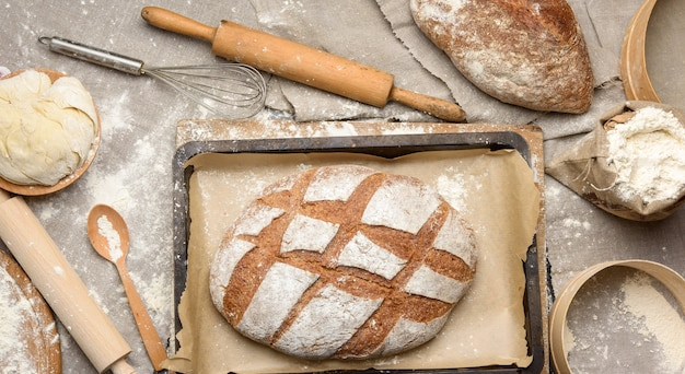 Bread, kneaded dough of white wheat flour lies on a wooden plate and a wooden rolling pin, top view