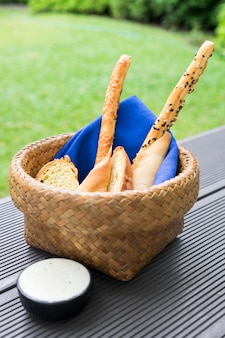 Bread loaf food snack in basket with blue napkin and white sauce