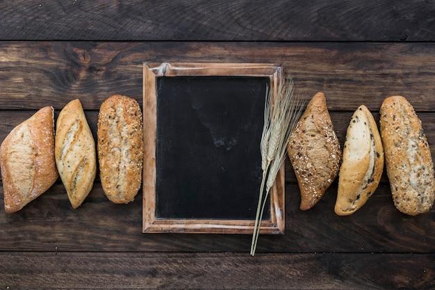 Bread loafs with chalkboard on desktop