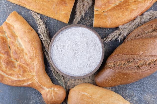 대리석 표면에 밀가루 한 그릇 주위에 빵 덩어리와 밀 줄기