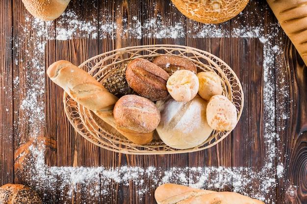 Хлебная корзина для хлеба внутри прямоугольной рамы из муки на деревянном столе