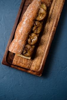 Pagnotta e fico lunghi del pane sul bordo di legno