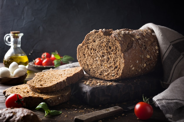 Bread, olive oil, tomato and basil on wooden cutting board
