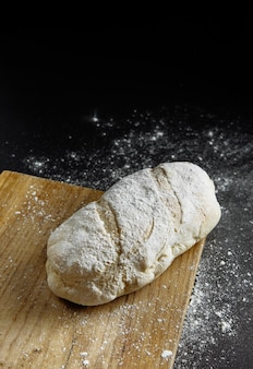 Хлеб на черном фоне муки на столе