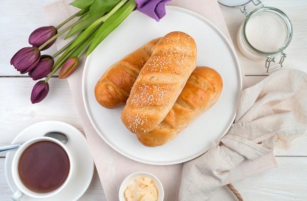 Хлеб на плоской тарелке, тюльпаны и чай на светлом деревянном фоне. вид сверху. концепция праздничных кулинарных фонов.
