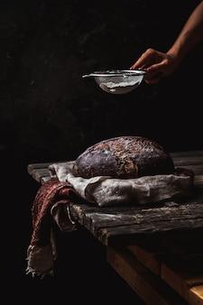 Хлеб по-деревенски на черном фоне. домашняя выпечка