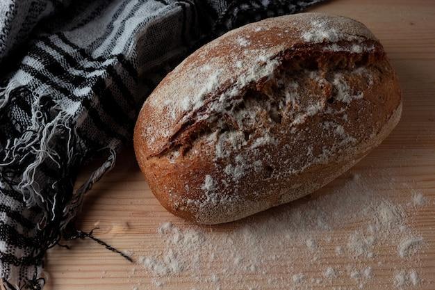 木製のテーブルの上のパンに小麦粉を振りかける