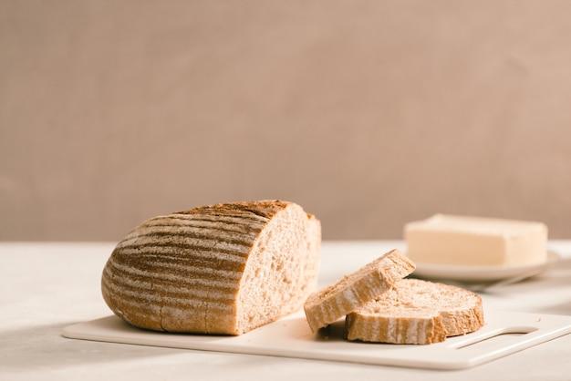 Хлеб на подставке для тарелок в окружении масла и молока на белом столе крупным планом