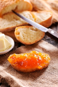 Bread and orange homemade jam on wooden table