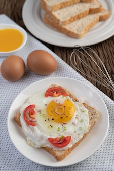 Bread placed with a fried egg with tomatoes, tapioca flour and sliced ​​spring onions.