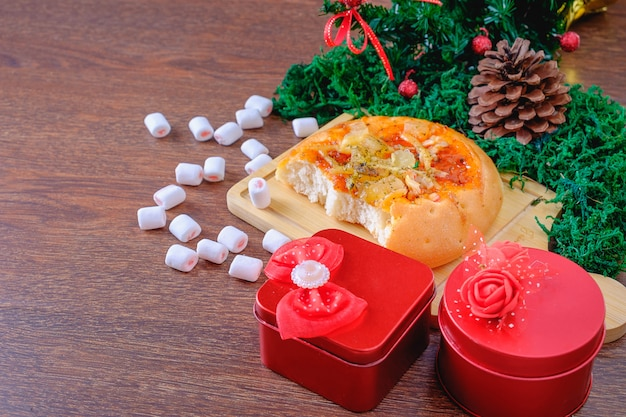 Bread and red gift box with christmas tree on a christmas tree