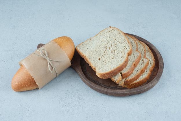 나무 접시에 빵 롤과 빵 조각