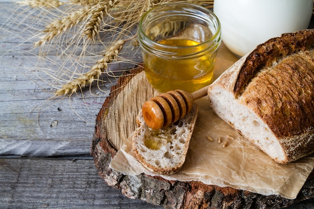 Bread, rye, wheat, honey, milk rustic wood background