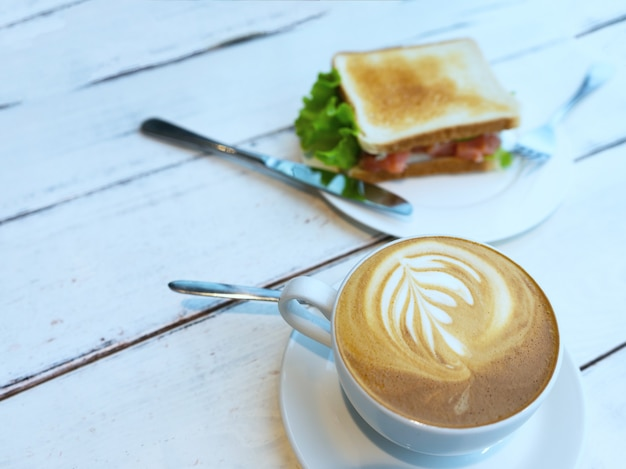 Bread sandwich with ham, cheese, cherry tomatoes, cucumber and lettuce and espresso coffee for breakfast. selective focus.