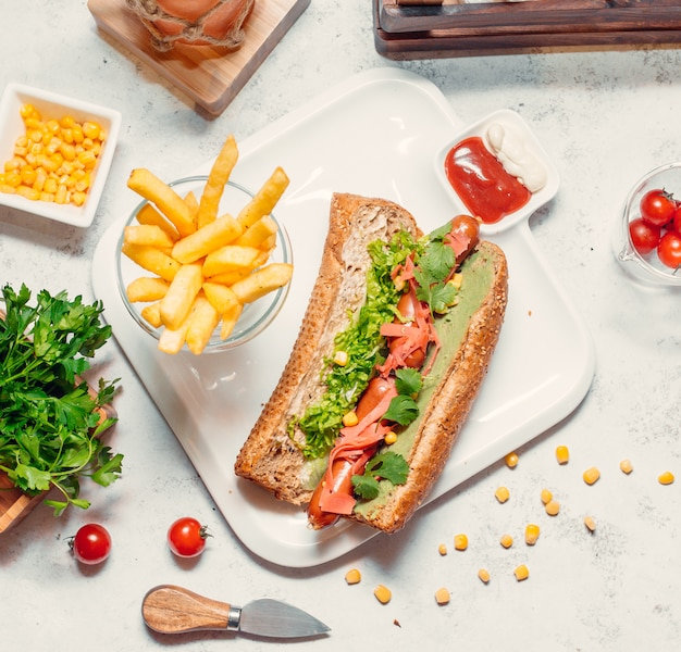 Bread sandwich with herbs and tomatoes and french fries around.