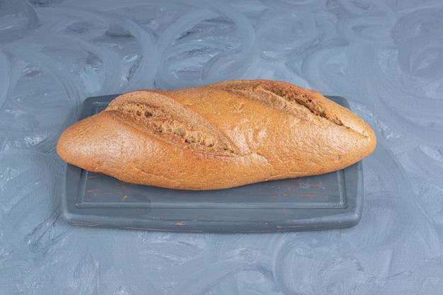 大理石のテーブルの上の海軍のトレイに座っているパン。