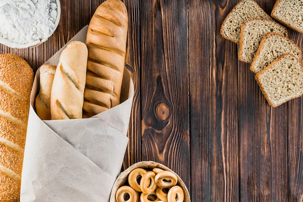 Bread slice, baguettes, bagels, flour on the wooden backdrop