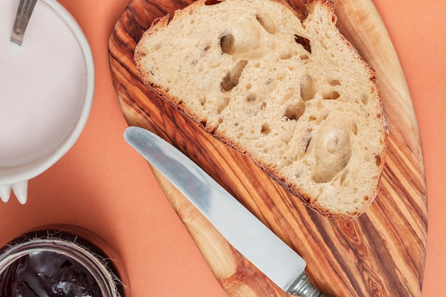 Bread slice and butter knife on chopping board with milk and jam on colored background