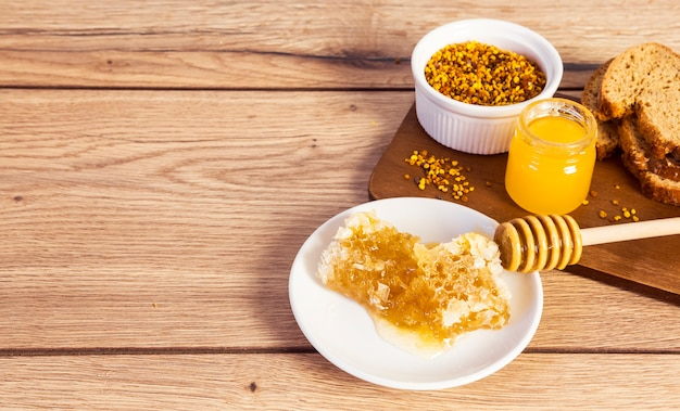 Bread slice with honey and honey accessories on wooden table