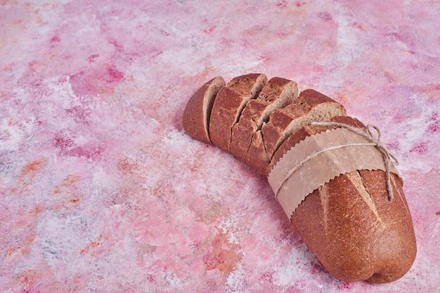 분홍색 테이블에 빵 슬라이스.