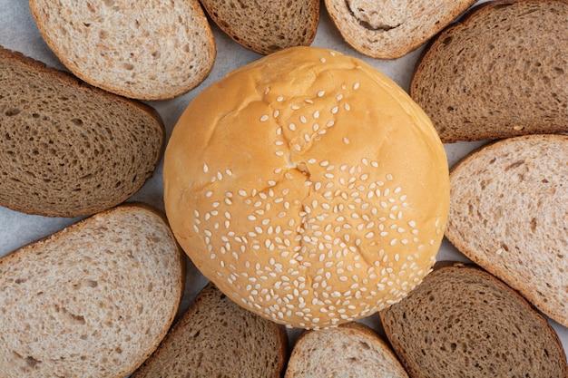 파란색 배경에 참 깨와 빵 조각과 롤빵. 고품질 사진