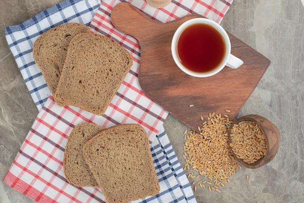 大麦とテーブルクロスの上のパンのスライスとお茶のカップ。高品質の写真
