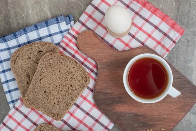 卵とテーブルクロスの上のパンのスライスとお茶のカップ。高品質の写真