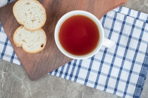 木の板にパンのスライスとお茶のカップ。高品質の写真