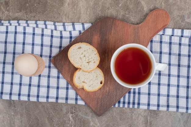 卵と木の板にパンのスライスとお茶のカップ。高品質の写真