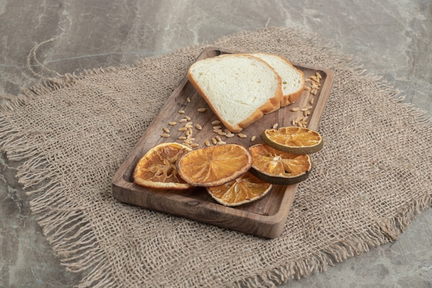 Ломтики хлеба и сушеный апельсин на деревянной тарелке. фото высокого качества
