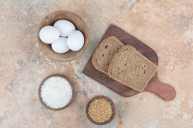 Bread slices, bowls of eggs, flour and barley on marble surface