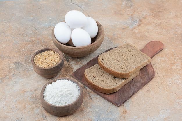 Ломтики хлеба, миски с яйцами, мукой и ячменем на мраморной поверхности