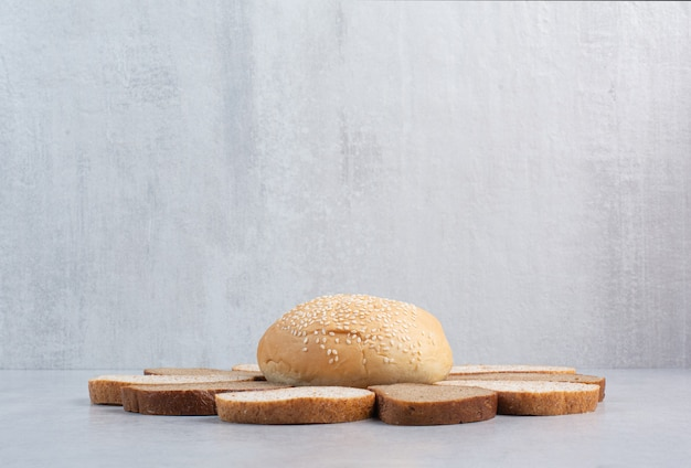 Bread slices and bun with sesame seeds on blue background. high quality photo
