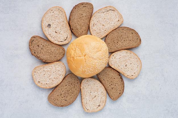 Fette di pane e panino con semi di sesamo sulla superficie blu