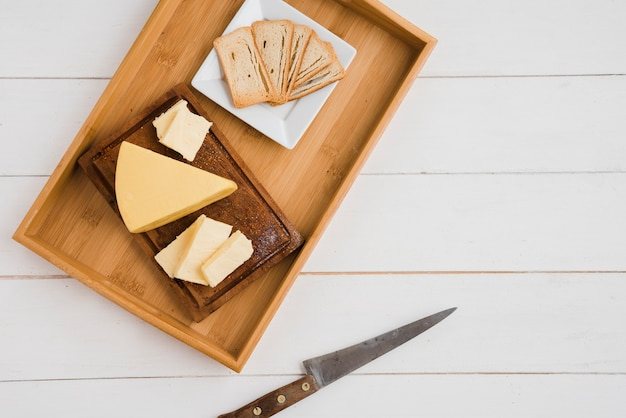 Bread slices and cheese wedges on wooden tray with knife