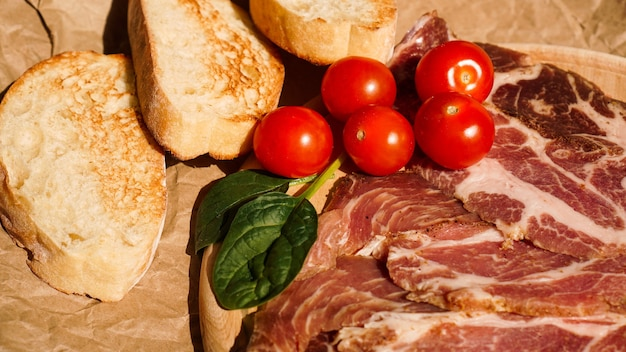 パンのスライス、チェリートマト、ほうれん草、ハム。サンドイッチやブルスケッタの材料。健康的な生鮮食品の調理