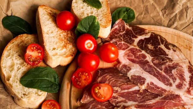 Ломтики хлеба, помидоры черри, шпинат и ветчина. ингредиенты для бутерброда или брускетты. приготовление здоровых свежих продуктов