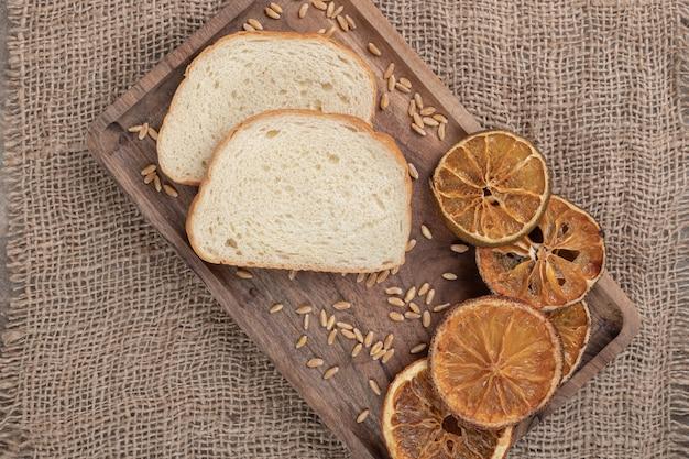 Fette di pane e arancia secca sul piatto di legno. foto di alta qualità