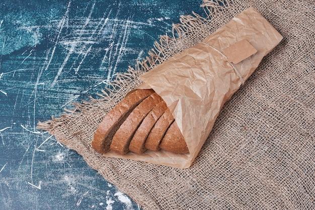 Ломтики хлеба в бумажной упаковке на синем столе.