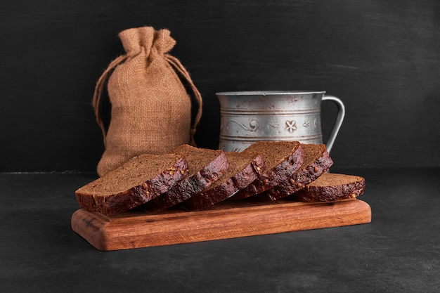 Ломтики хлеба на деревянном блюде.