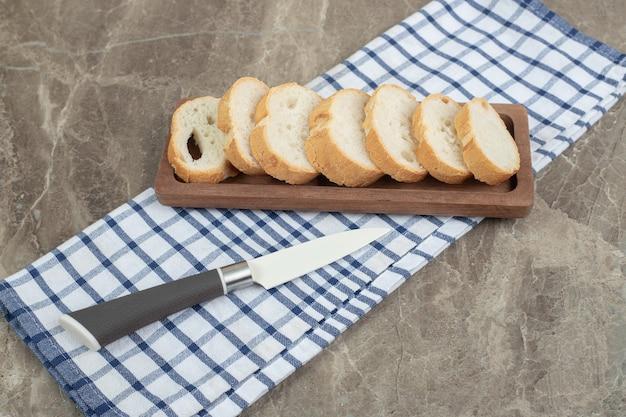 칼으로 나무 접시에 빵 조각입니다. 고품질 사진