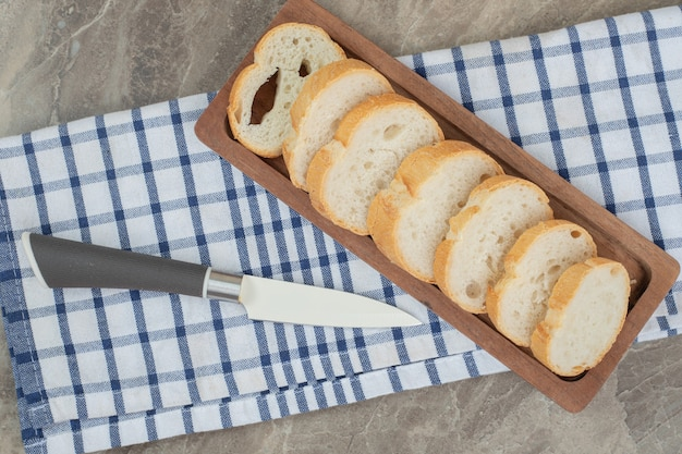 ナイフで木の板にスライスしたパン。高品質の写真