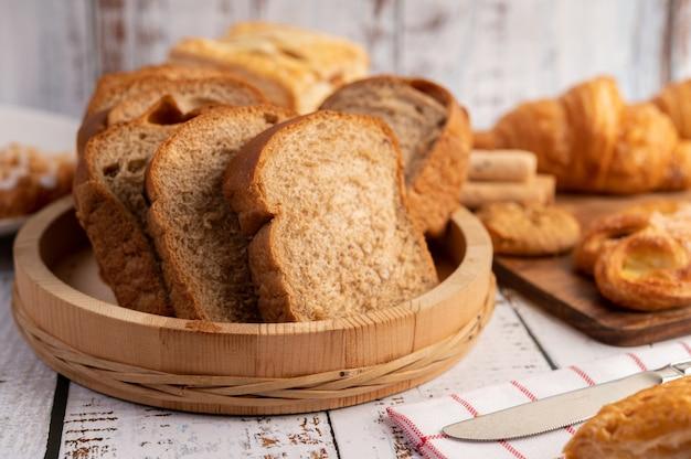 Ломтики хлеба размещены в деревянной тарелке на белом деревянном столе.