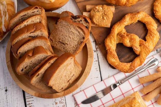 白い木製のテーブルの上の木製のプレートに置かれたパンのスライス。