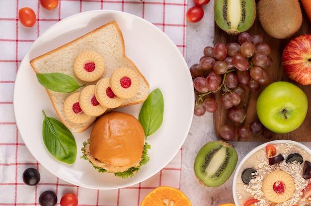 Ломтики хлеба, булочки с начинкой и гамбургеры на белой тарелке.
