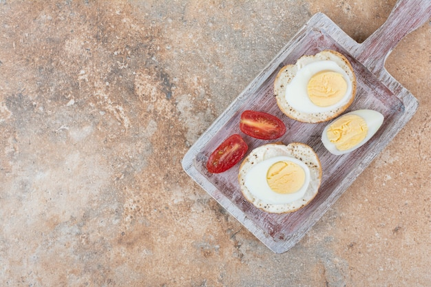Bread slices with boiled eggs and tomato slices on wooden board